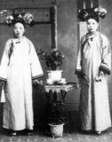 Manchu women of the Forbidden City or Gugong in Beijing pose for a photograph c. 1890 during the Manchu Qing Dynasty (1644-1911). They wear elaborate and expensive dresses. Their faces are whitened with powder, and their lipstick is applied in a narrow band across the centre of their lips following the fashion of the time.